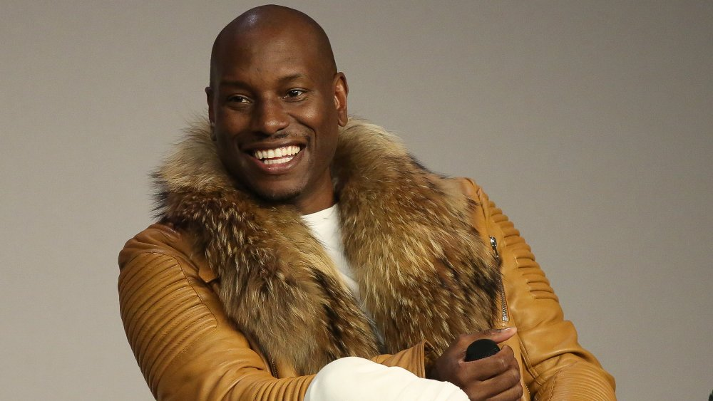 Tyrese Gibson smiling big, wearing a light brown leather jacket during an interview