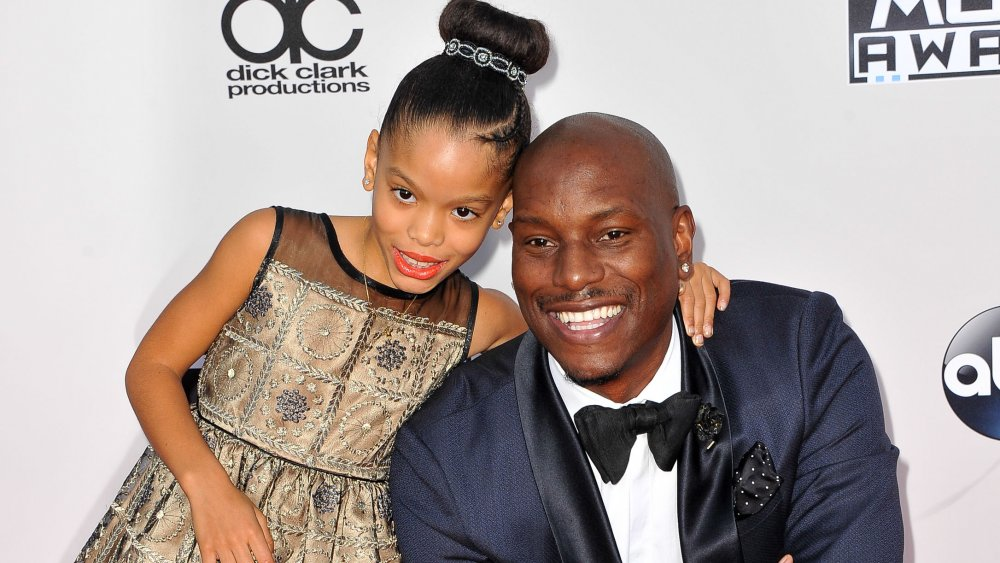 Tyrese Gibson in a blue suit, smiling and kneeling on the red carpet next to daughter Shayla Gibson