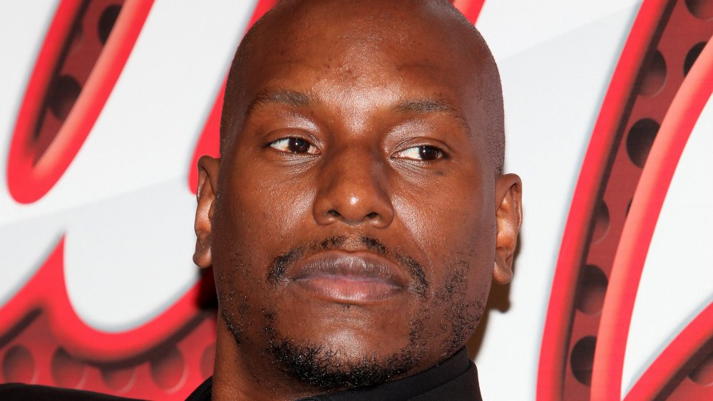 Tyrese Gibson in an all-black suit, with a serious expression, sitting back during an interview
