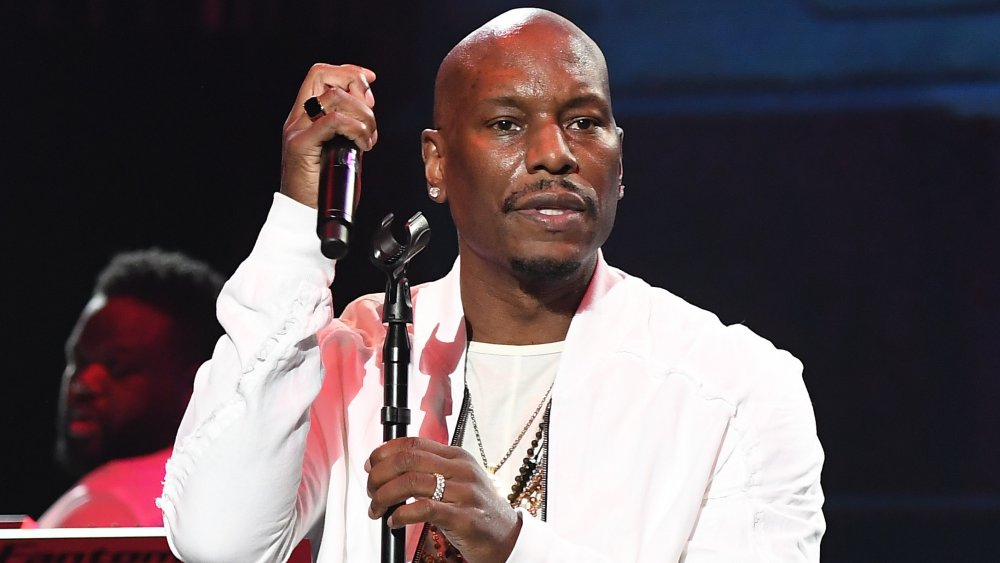 Tyrese Gibson in an all-white outfit, looking out into the audience during a live performance with a serious expression