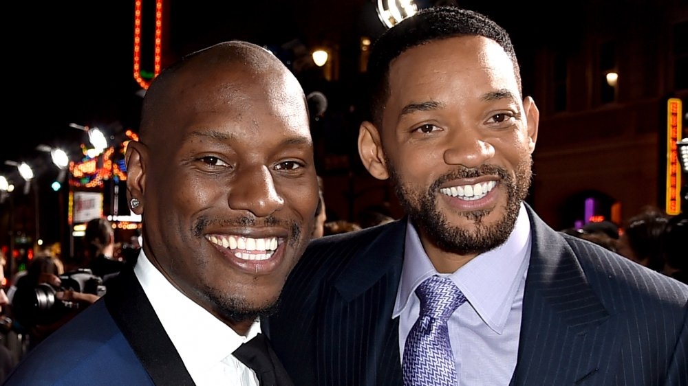 Tyrese Gibson and Will Smith, both in blue suits and smiling at an event with their arms around each other