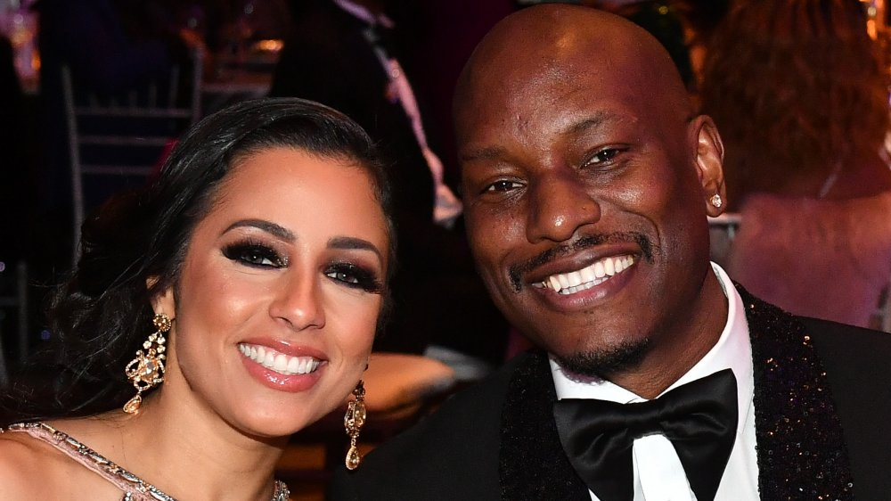Samantha Lee Gibson in a bejeweled dress, Tyrese Gibson in a black, sparkly suit, both smiling and leaning into one another