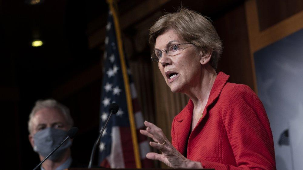 Sen. Elizabeth Warren i en rød blazer, snakker under en politisk begivenhet