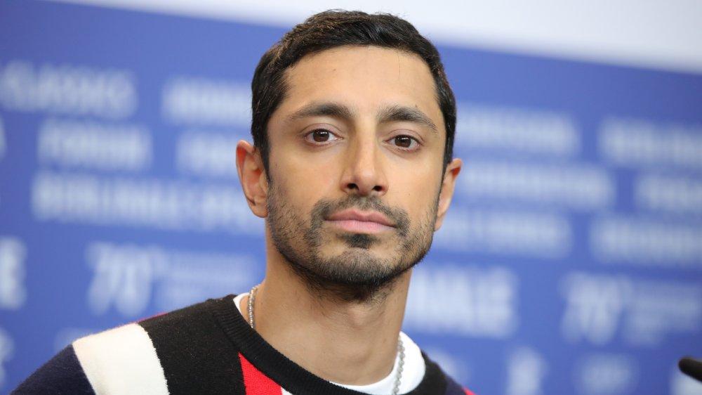 Riz Ahmed i en svart, rød og hvit genser, poserer under et intervju med et nøytralt uttrykk