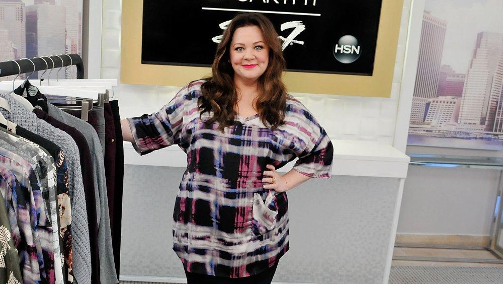 Melissa McCarthy poserer ved siden av et klesstativ for sin Seven7 kleskolleksjon