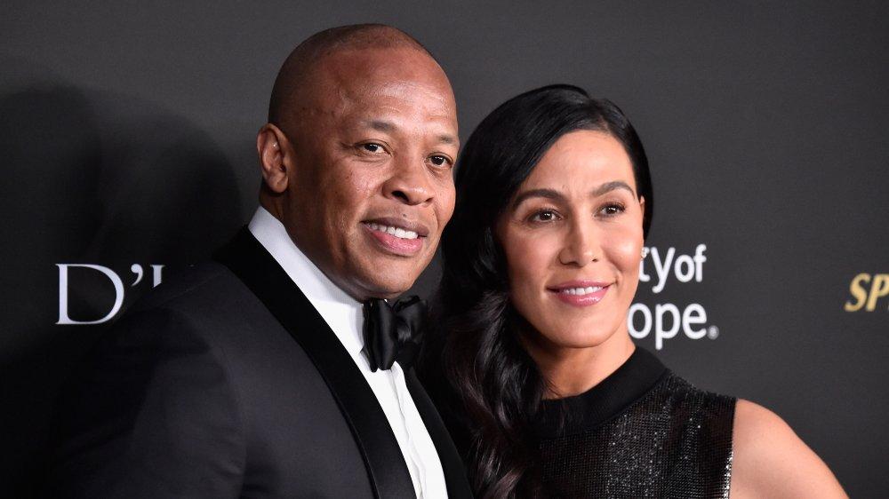 Dr. Dre og Nicole Young poserer arm-i-arm og smiler på den røde løperen