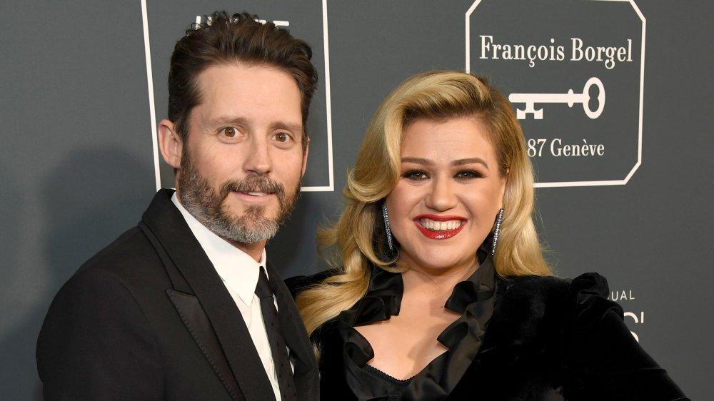 Brandon Blackstock og Kelly Clarkson, begge smiler mens de poserer arm-i-arm på den røde løperen