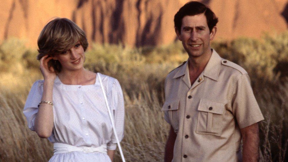 Prinsesse Diana og prins Charles smiler mens de står langt fra hverandre