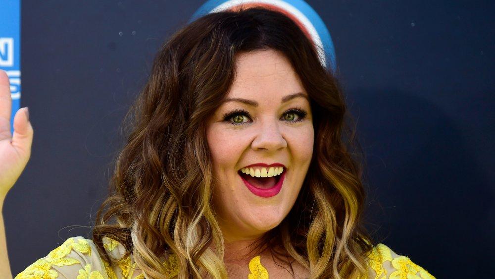 Melissa McCarthy i en gul kjole, smiler stort og vinker