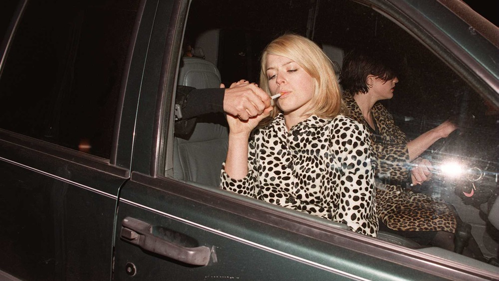En mann tenner sigaretten til Amanda de Cadenet
