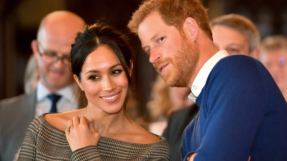 Meghan Markle ler i en skulderfri topp mens prins Harry hvisker i øret hennes