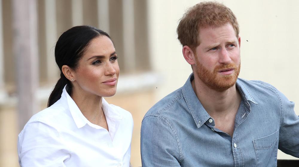 Meghan Markle i hvitt sitter ved siden av prins Harry i en jeanskjorte mens de ser ettertenksomt ut på et arrangement