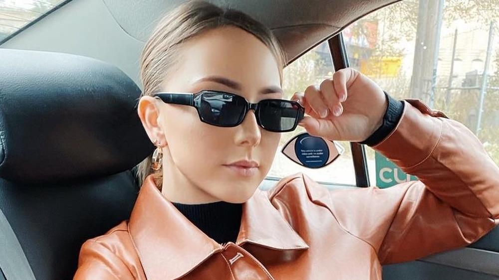 Hailie Mathers i baksetet på bilen, solbriller på