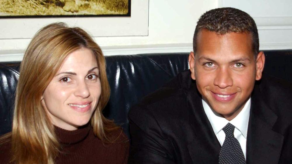 Cynthia Scurtis og Alex Rodriguez satt på en sofa og smilte