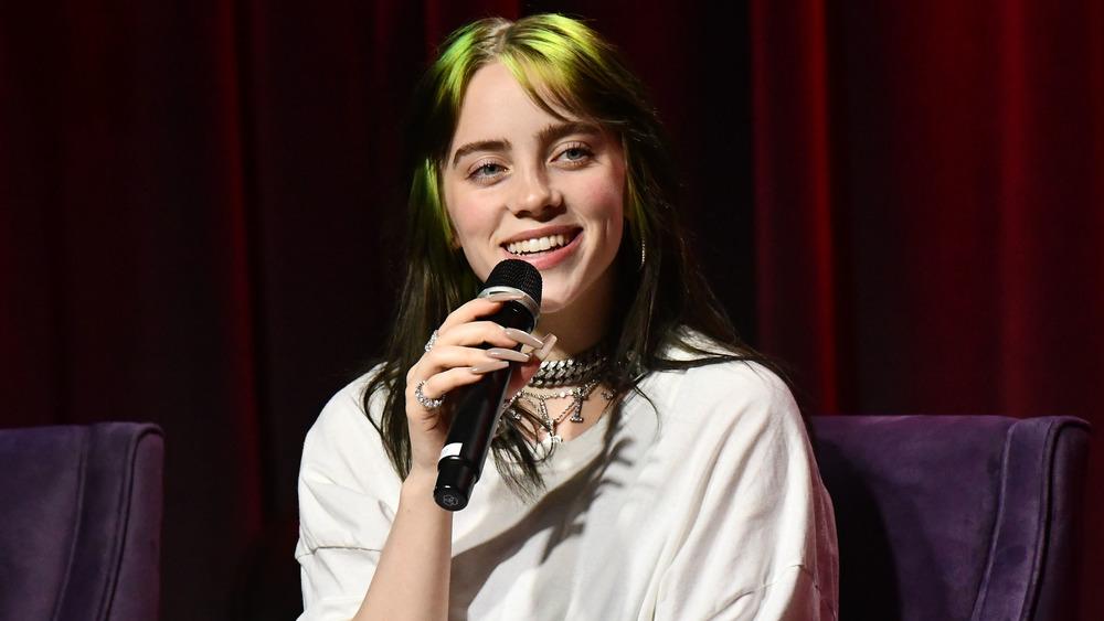 Billie Eilish smiler og holder en mikrofon