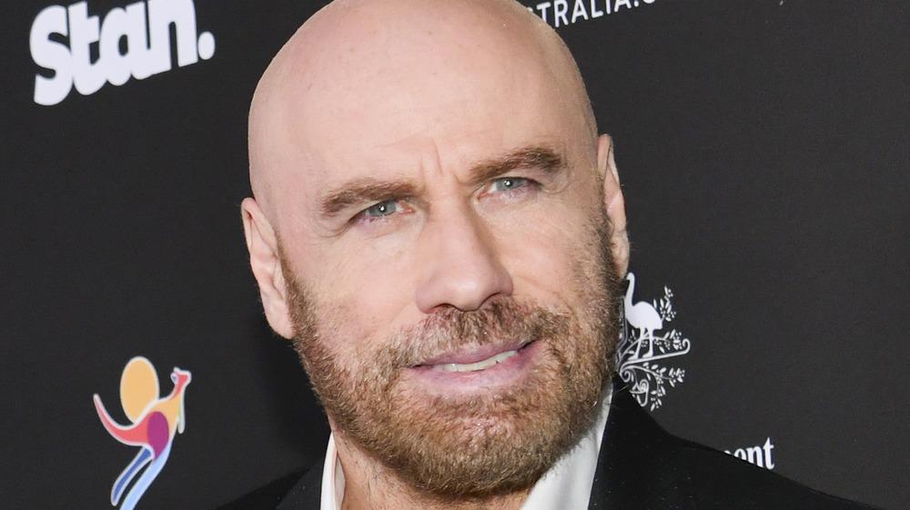 John Travolta stiller opp for et bilde på den røde løperen