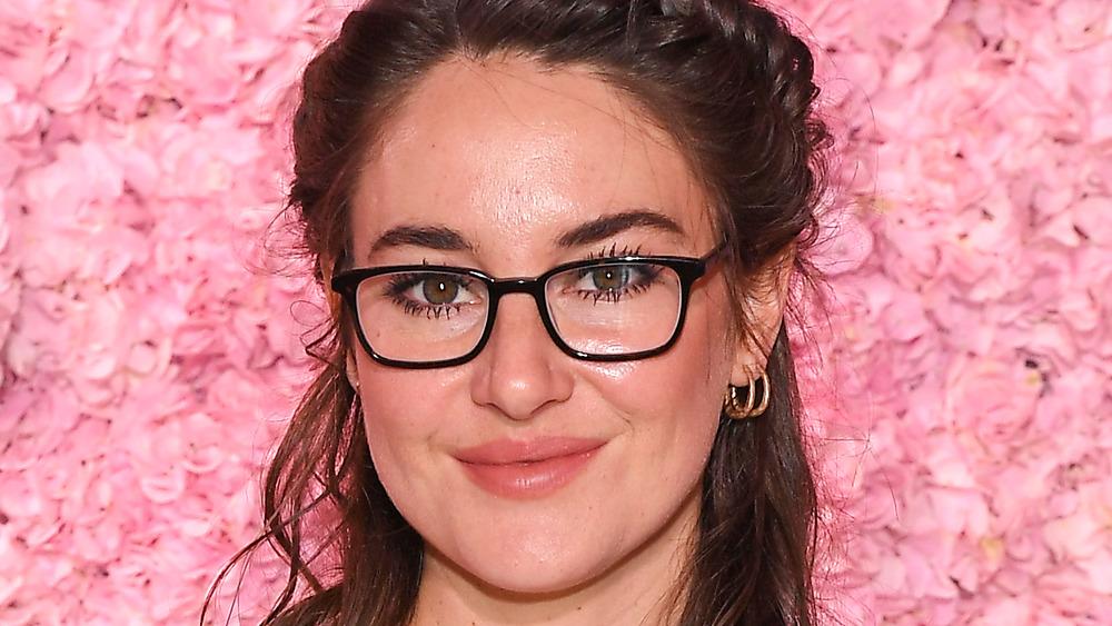 Shailene Woodley står mot en vegg av rosa roser med briller