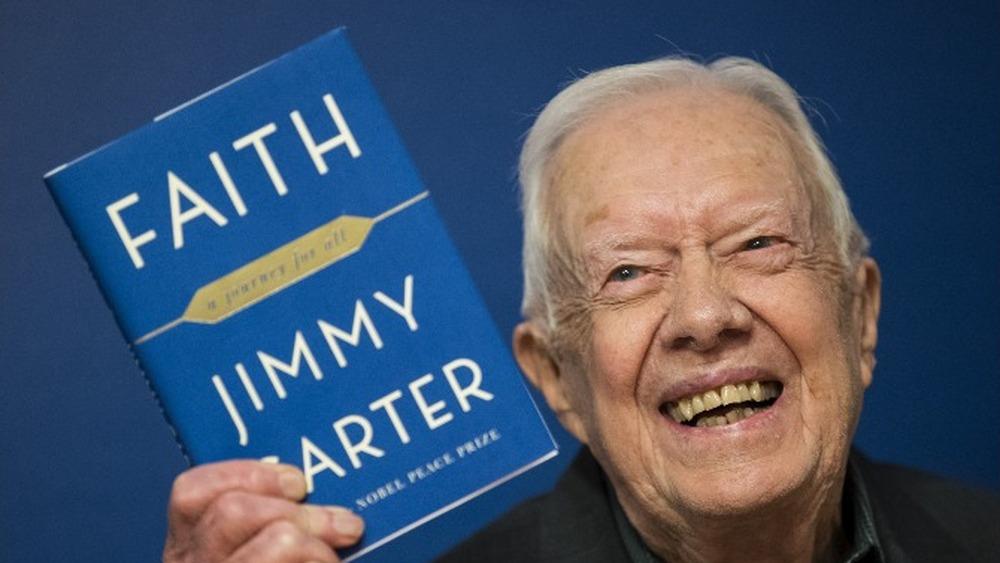 Tidligere amerikanske president Jimmy Carter holder opp en kopi 'Faith: A Journey For All' på et boksigneringsarrangement i 2018