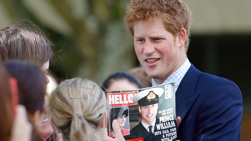 Prins Harry holder et bilde av prins William i en tabloid