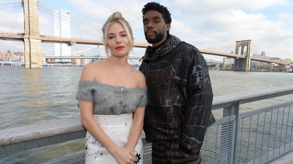 Sienna Miller og Chadwick Boseman foran broen