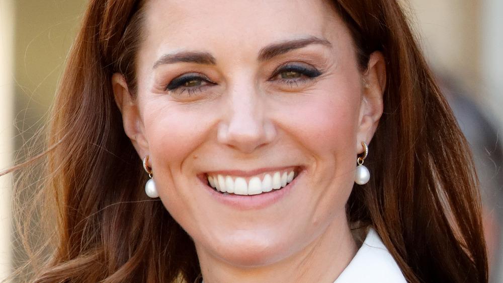 Kate Middleton smiler mens hun har på seg perleøreringer