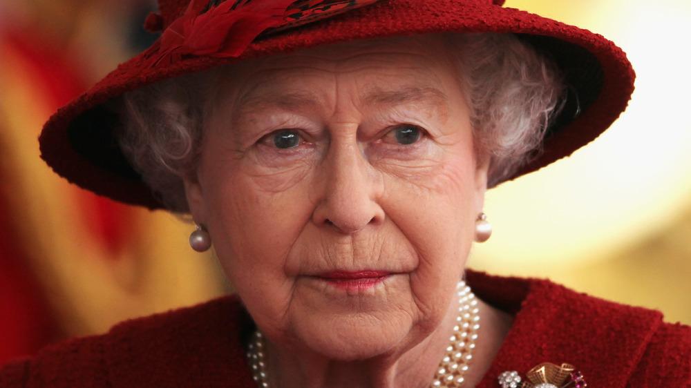 Dronning Elizabeth ser akter i en hatt og perler