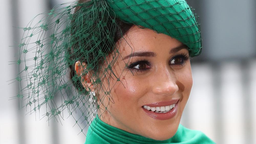 Meghan Markle smiler i grønn hatt