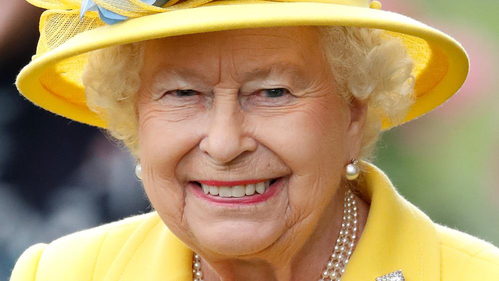 Dronning Elizabeth II smilende i gult antrekk og matchende lue