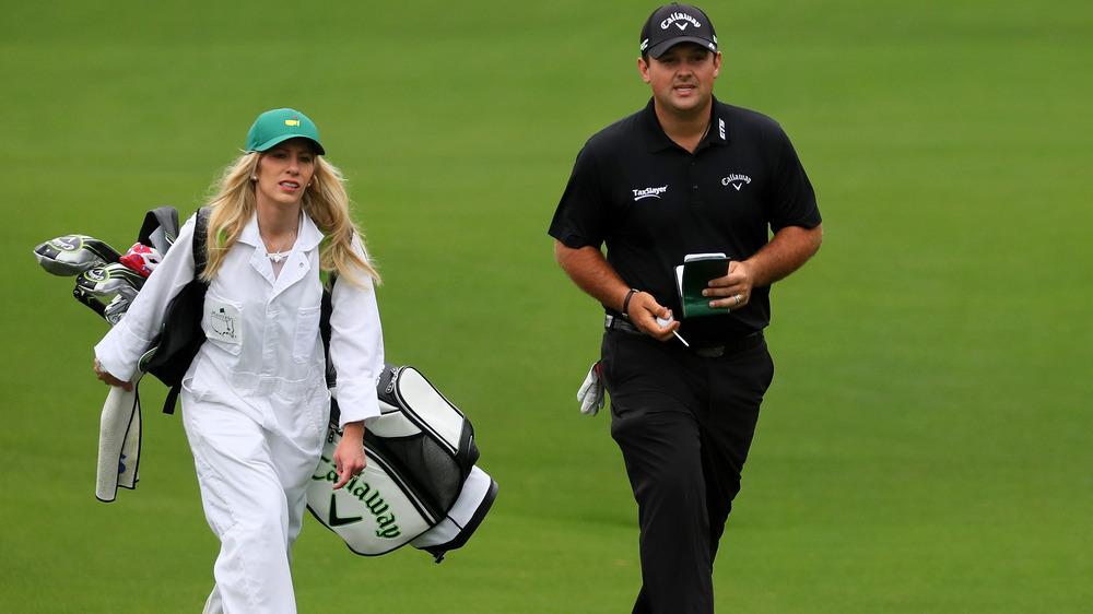 Justine Reed, jobber som caddie, iført helt hvitt, iført hat, holder golfkøller;  Patrick Reed, iført svart og hatt, på golfbanen