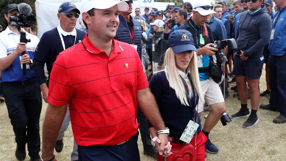 Patrick Reed og Justine Reed går hånd i hånd, begge iført hatter, omgitt av fotografer og fans