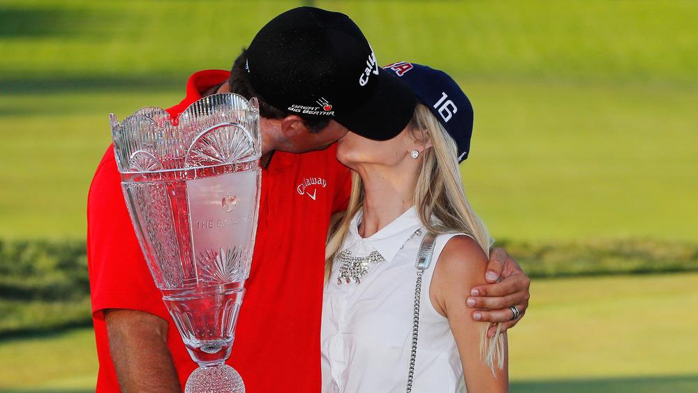 Patrick Reed og Justine Reed kysset, begge iført hatter, på golfbanen, iført hatter