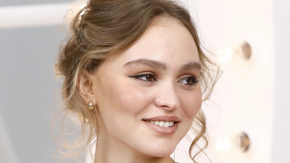 Lily-Rose Depp smiler mot kameraene på et motebegivenhet