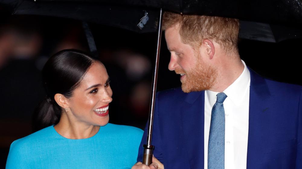 Meghan Markle og prins Harry ler under paraplyen