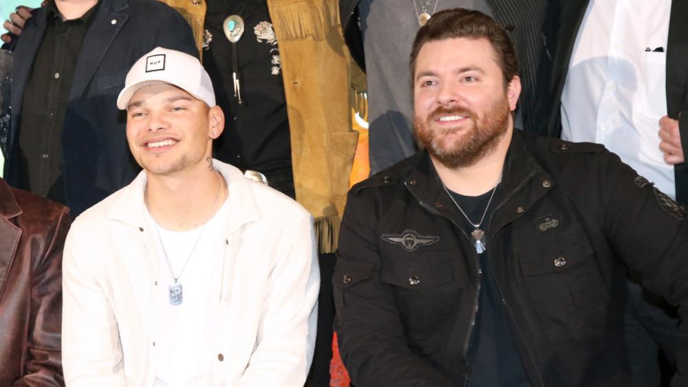 Kane Brown og Chris Young smiler sammen mens de stiller på et arrangement
