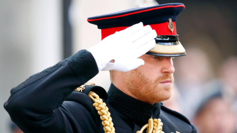 Prins Harry, i full militæruniform, hilser og ser seriøs ut