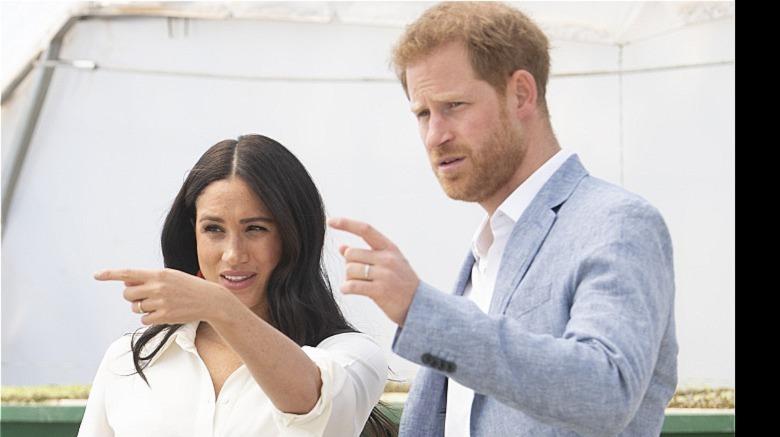 Meghan Markle og prins Harry peker med fingrene