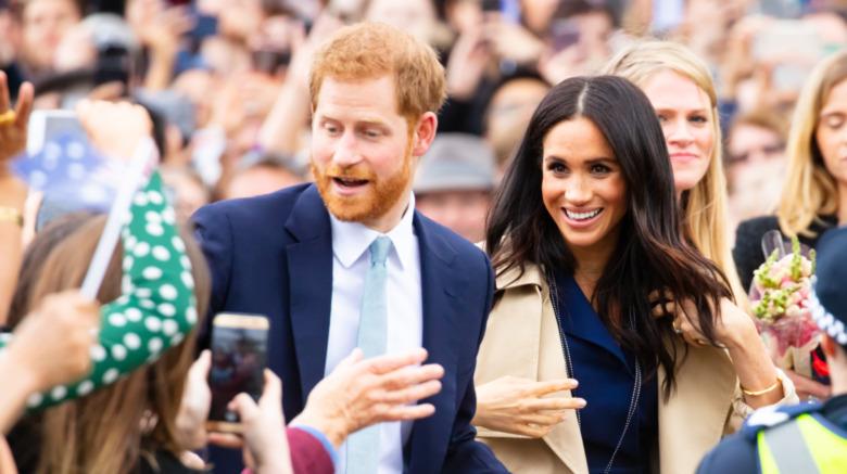Prins Harry og Meghan Markle hilser på en mengde