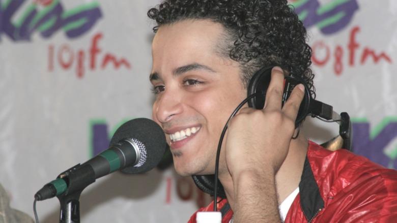 Mario Vasquez foran en mikrofon og holder hodetelefoner i ørene