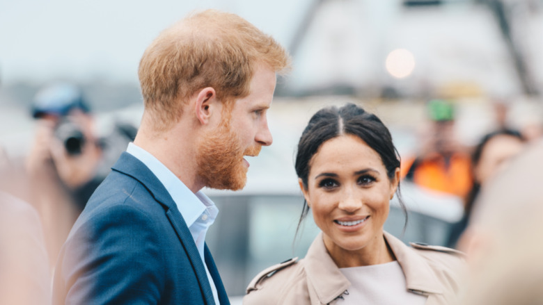 Prins Harry og Meghan Markle smiler i en mengde