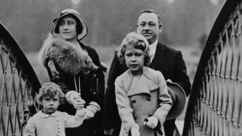 Dronning Elizabeth går en hund nær søsteren og moren i 1933.