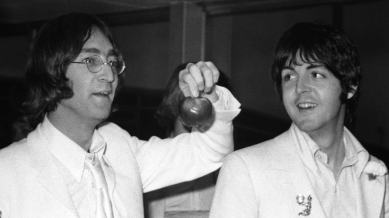 John Lennon holder et eple mens Paul McCartney smiler