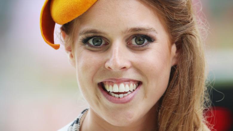 Prinsesse Beatrice smiler i en oransje hatt