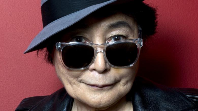 Yoko Ono poserer i skinnjakke, briller og hatt.