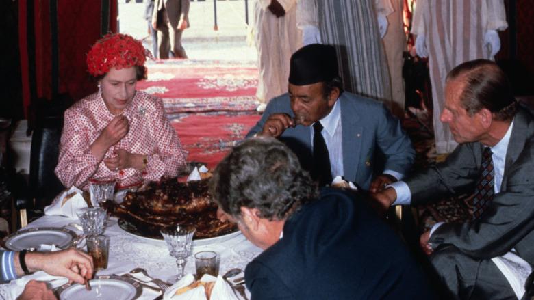 Dronning Elizabeth spiser med hendene som ser ulykkelige ut