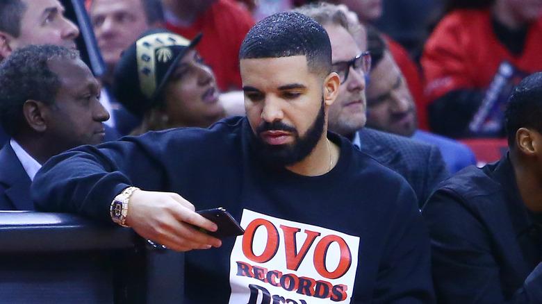 Drake ser på telefonen sin
