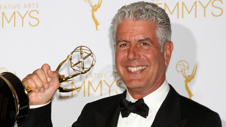 Anthony Bourdain smiler og holder en Emmy