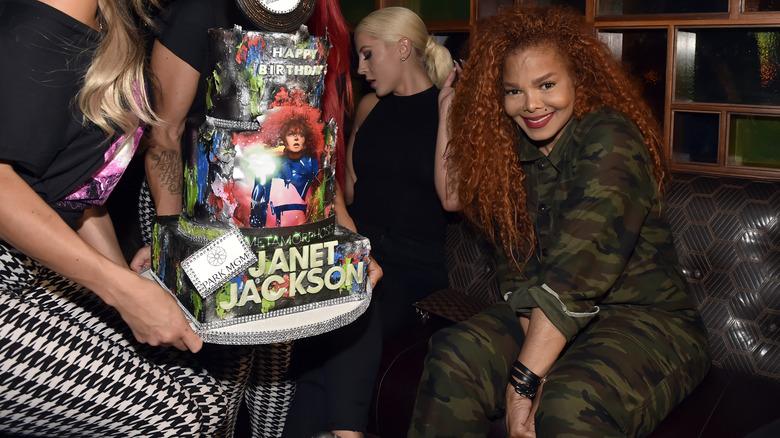 Janet Jackson smiler ved siden av bursdagskaken sin