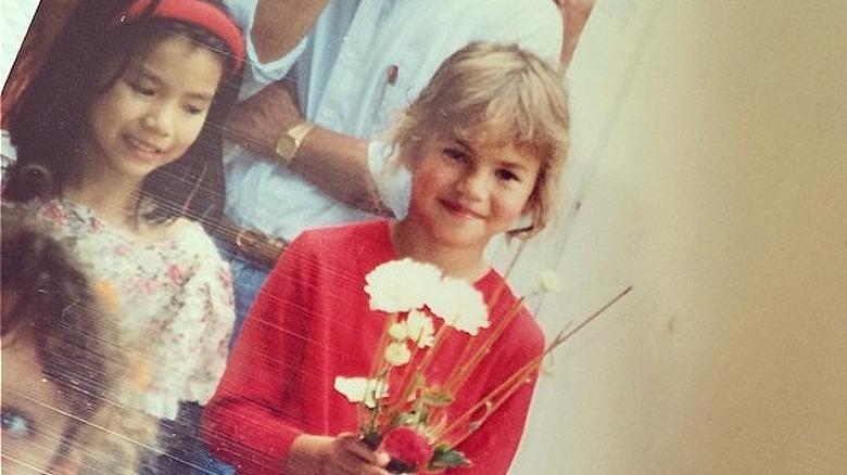 Chrissy Teigen som barn som holder blomster