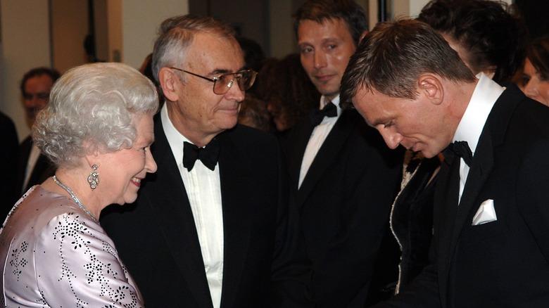 Dronning Elizabeth smiler og gir Daniel Craig et håndtrykk