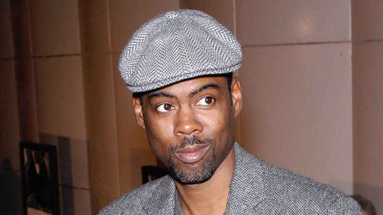 Chris Rock i en grå hatt og dress